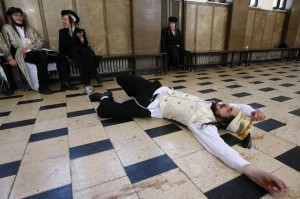 An ultra-Orthodox Jew lies on the ground drunk during celebrations for the Jewish holiday of Purim in a synagogue in Jerusalem
