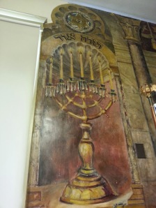 "On each side of this artistic display are two depictions of candelabras. This one says ""Torah Ohr,"" or ""The Light of Torah."" The matching one says ""Ner mitzvah,"" calling to mind the ritual lights of the sabbath and festival days."