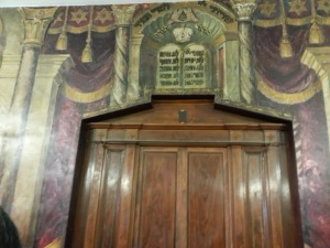 "The restored Aron haKodesh - the ark for the Torah scrolls. The murals also senselessly restored. It shows tablets of the Ten Commandents. Above is the words ""Shivit Hashem Negedi Tadmi"" which means ""I will place [the name of'] the Lord before me at all times."""